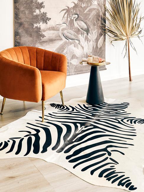 Vloerkleed in zebraprint naast een fluwelen fauteuil in oranje kleur