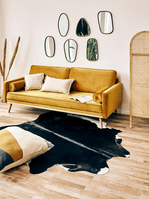 Een woonkamer met gele zitbank met sierkussens in beige met vloerkleed in dierenprint