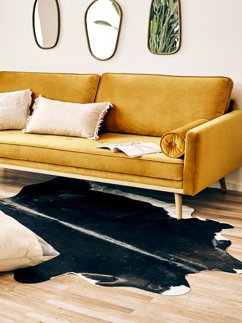 Zitbank in geel met sierkussens in beige met vloerkleed in dierenprint
