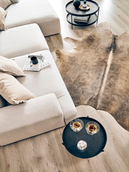 Fluwelen fauteuil in beige kleur naast zwarte bijzettafel