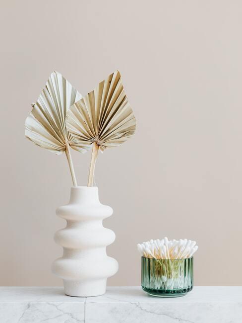 Witte vaas op witte dressoir naast een groene houder