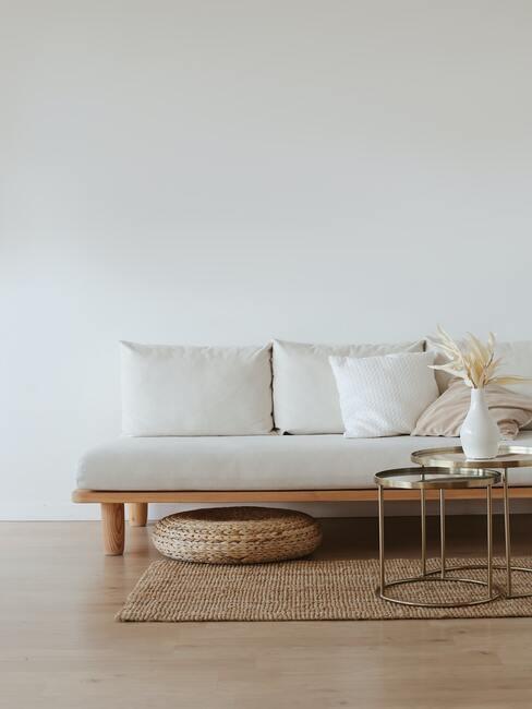 Woonkamer in beige met comfortabele zitbank en rotan poef