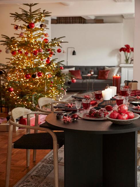 Tradiotionele groen met rode kerstboom en eetkamertafel setting met wijn en spijs