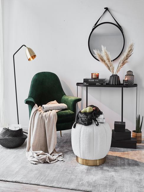 Boucle witte poef naast een groene fluwelen fauteuil met beige zachte plaid naast vloerlamp en zwarte sideboard met decoraties