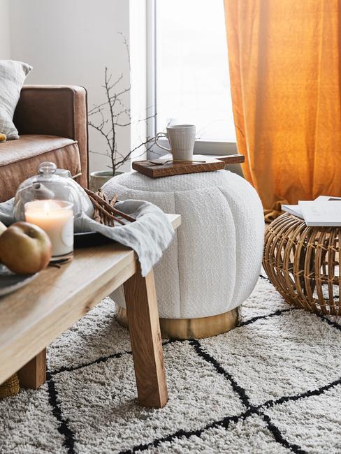 Poef op wit vloerkleed in woonkamer in boho-stijl