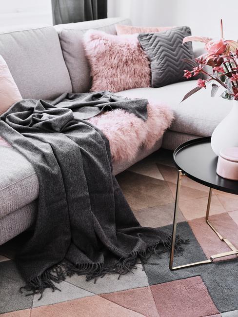 Zachte grijze plaid op grijze zitbank naast een zwarte bijzettafel met vaas met bloemen