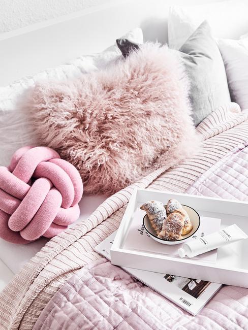 Zachte kussens in roze op het bed