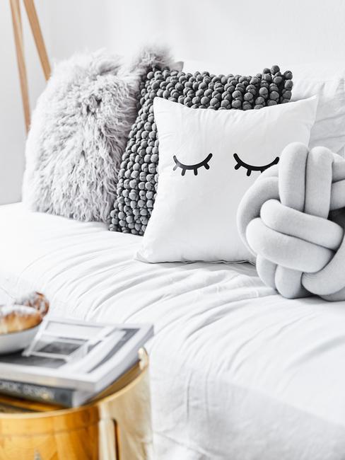 Zachte sierkussens in wit en grijs op zitbank in moderne woonkamer