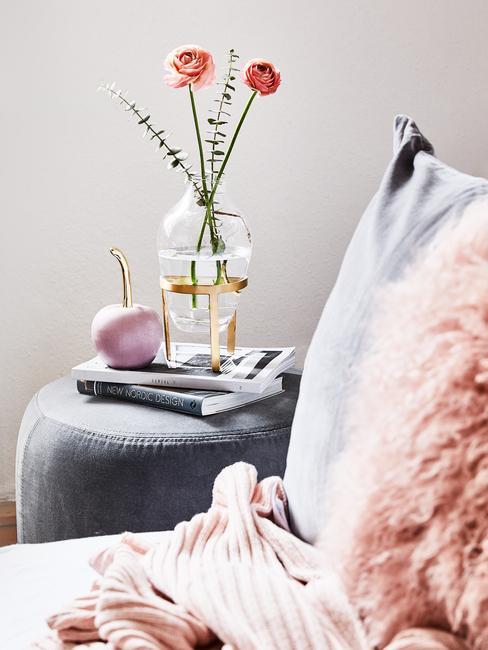 Zachte plaid op zitbank in grijs met kleurrijke sierkussens en metalen bijzettafel in moderne woonkamer