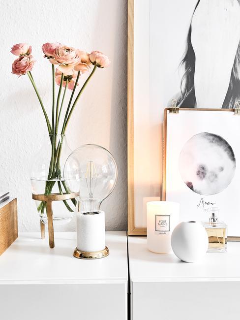 Transparante glazen vaas met takken op wit dressoir