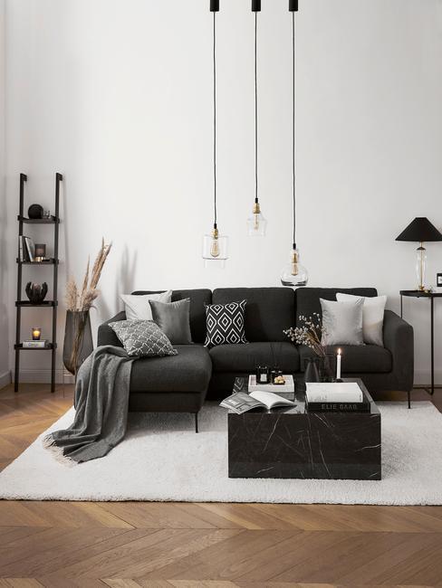 Glazen hanglampen boven zitbank in zwart en decoratieve ladder