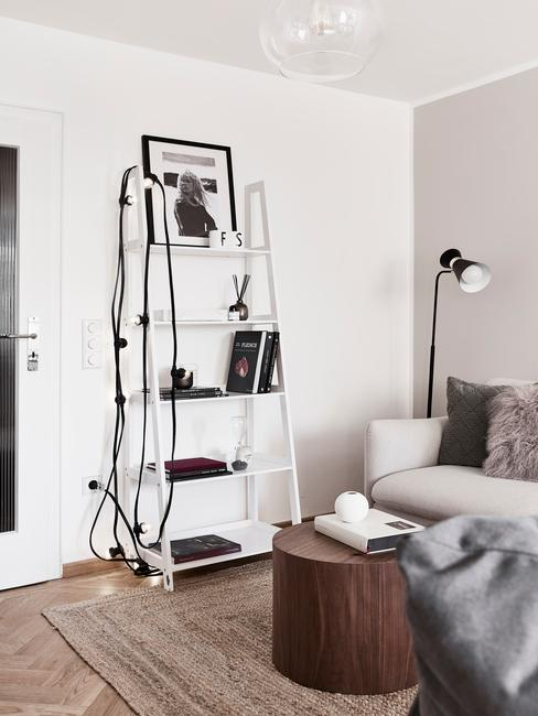 Decoratieve ladder in wit naast een zitbank in beige