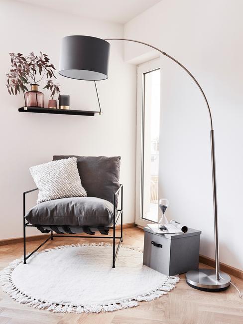 Zwarte metalen fauteuil met sierkussen in beige naast een vloerlamo
