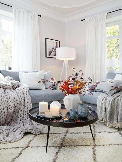 Woonkamer in Scandinavische stijl met comfortabele zitbank en zachte plaid naast een salontafel in zwart met kaarsen en bloemen in vaas in wit