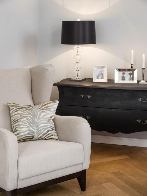 Comfortabele fauteuil in beige naast een sideboard in zwart in design woonkamer