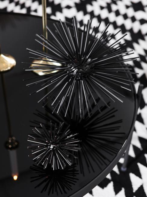 Decoratieve objecten op zwarte bijzettafel op vloerkleed