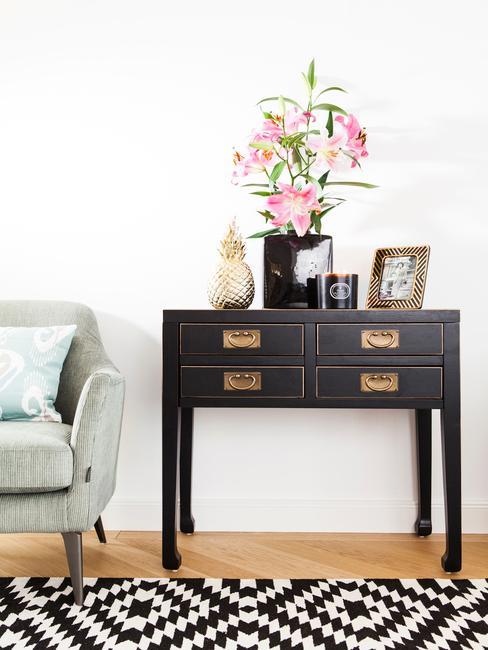 Sidetable in zwart met decoratieve objecten en bloemen in vaas naast een fluwelen bank in design woonkamer
