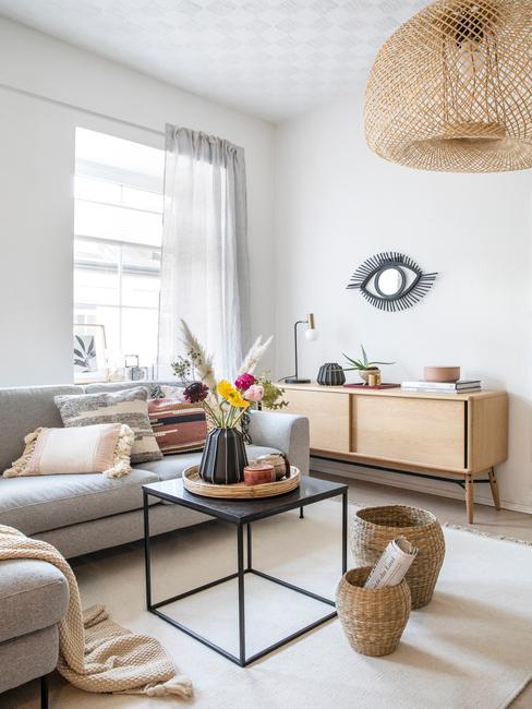 Rotan hanglamp boven een metalen salontafel in zwart en grijze zitbank in landelijke woonkamer