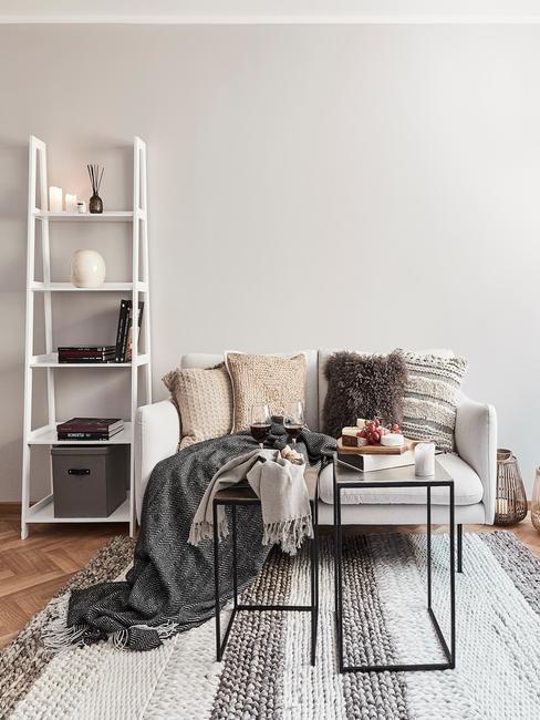 Landelijke woonkamer in beige met zitbank met sierkussen in beige en bordeaux kleur en decoratieve ladder in wit