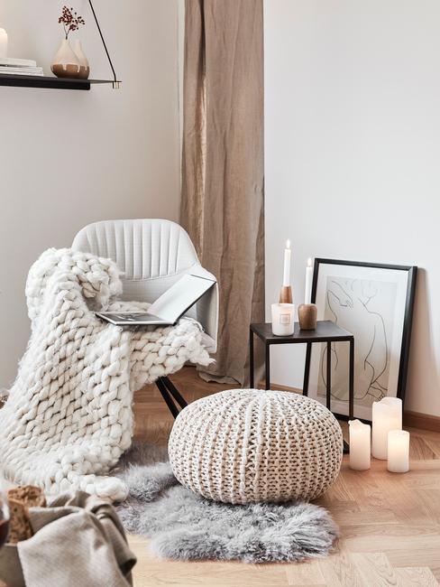 Fauteuil in wit met zachte plaid in wit naast een poef op schapenvacht in grijs