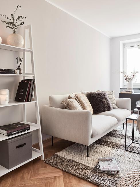 Woonkamer in beige met zitbank met sierkussen in beige en bordeaux kleur en decoratieve ladder in wit