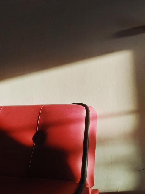 Leer schoonmaken: rood leren fauteuil in de schaduw