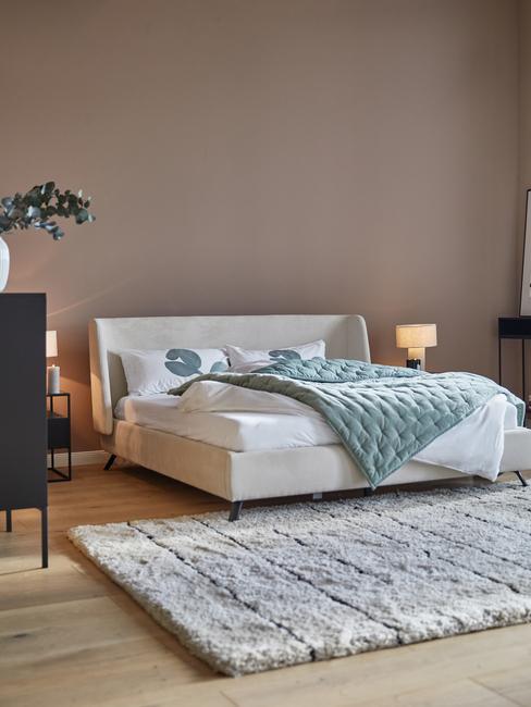 Slaapkamer met taupe muur en wit fluwelen bed