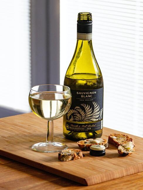 Eeen fles witte wijn op de tafel naast een wijnglas