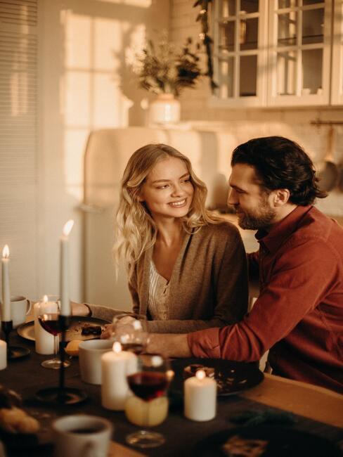 Wijngids: paar wijn drinken in de keuken aan een houten tafel met veel kaarsen