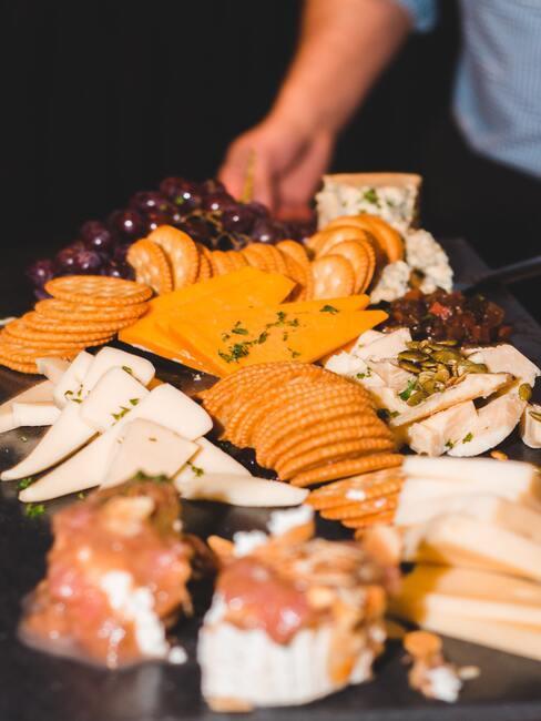 Kaasplank met diverse kazen en olijven, tomaten en andere snacks