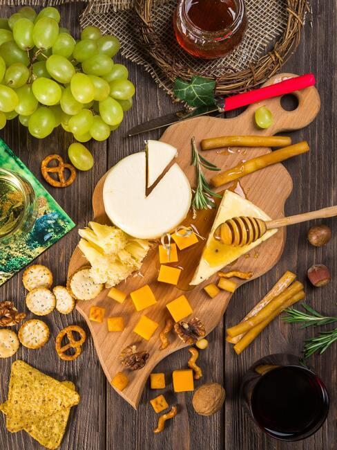 Kaasplank met diverse kazen en olijven, druiven en andere snacks en rode wijn in wijnglas