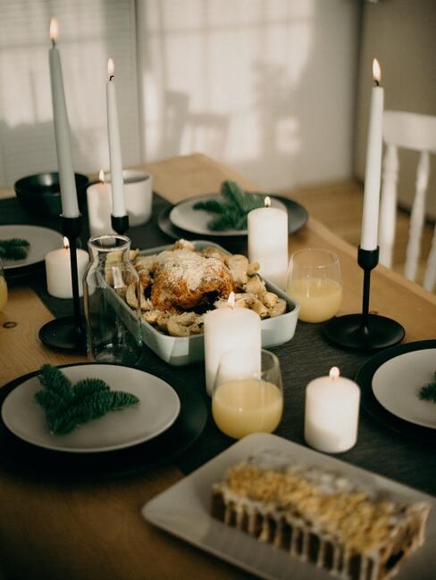 Kerstdiner in de woonkamer op een tafel zonder tafelkleed met wit porseleinen serviesgoed