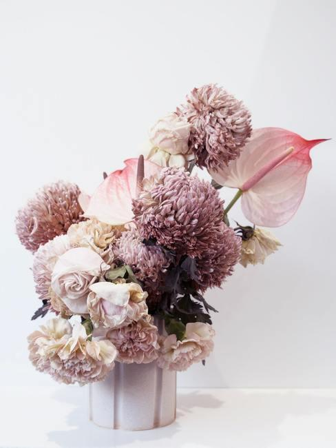Decoratie van kunstbloemen in een witte vaas in de boho-stijl