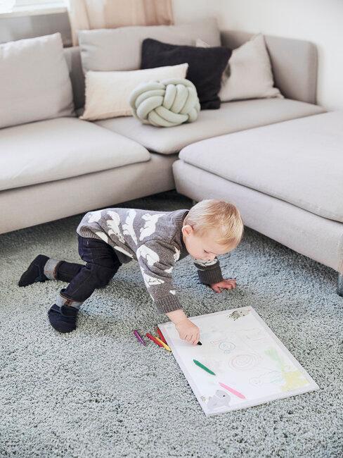 Jongens slaapkamer jongen in woonkamer met grijs vloerkleed en beige bank