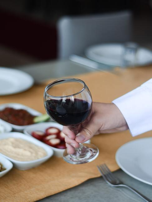Een vrouw met een glas wijn in haar hand op een achtergrond van snacks op een houten tafel