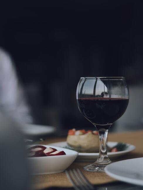Decanteren: rode wijn in glas op de houten tafel naast verschillende hapjes