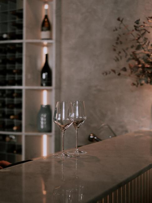 Twee wijnglazen op de achtergrond van wijnflessen