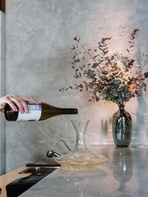 Decanteren: een vrouw die wijn in een karaf giet op de achtergrond van een vaas met bloemen