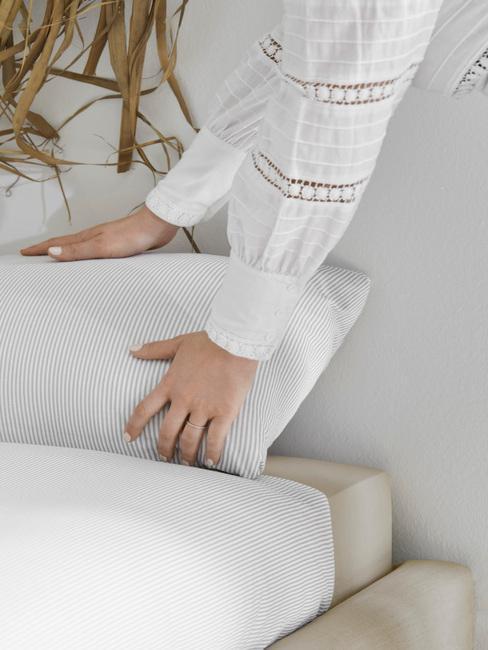 vrouw die een wit bed opdekt