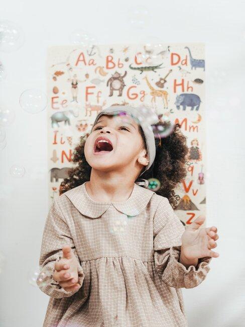 Lachend kind met alfabet poster op de achtergrond