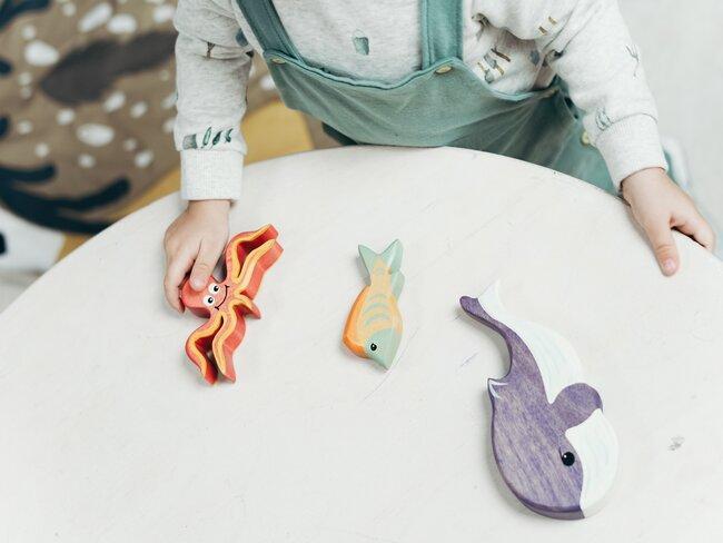 close-up kinderhand speelt met houten zeedieren op witte tafel