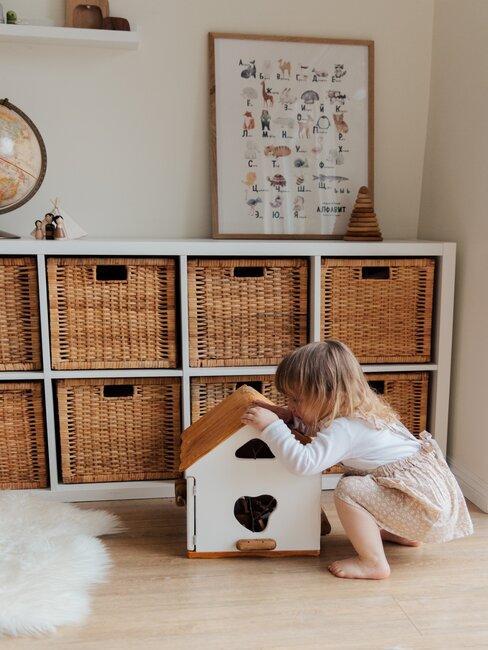 Kind speelt in kleuterkamer met kast met rotan manden op de achtergrond