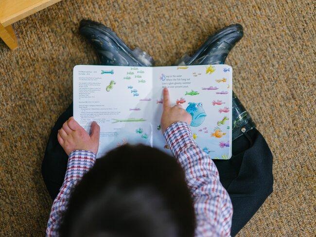 Kind leest boek op de grond