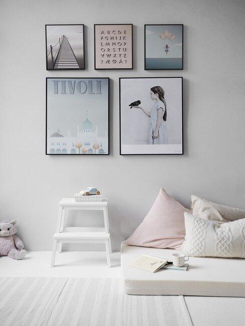 Meisjes slaapkamer met matras en kussens, prints aan de muur en trapje