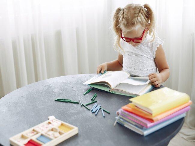Meisje leest en kleurt aan tafel met raam op de achtergrond
