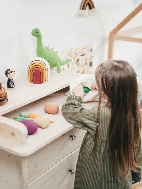 Meisje speelt met groenten speelgoed op houten bureau met speelgoed op de achtergrond