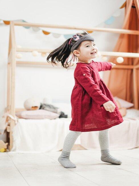 Meisje in rode jurk speelt in meisjes slaapkamer met bed op de achtergrond