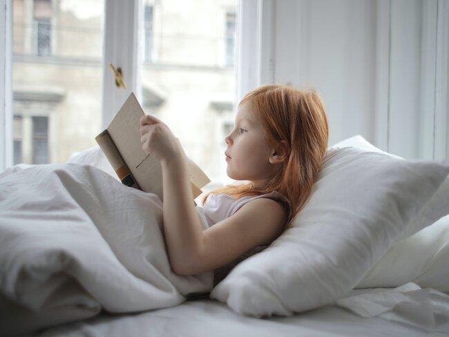 Meisje met rood haar leest boek in bed met raam op de achtergrond in wit