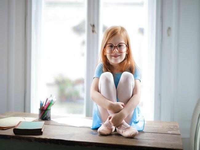 Meisje met bril zit op bureau met raam op de achtergrond
