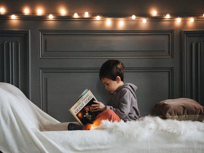 jongen leest in bed met witte lakens, lichtslinger en en groene achtergrond